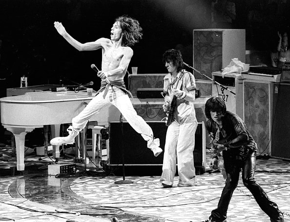 Mick Jagger leaping as Rolling Stones performat Madison Square Garden, NYC. June 24, 1975. (L-R) Mick Jagger, Ronnie Wood, Keith Richard. (Photo by Ron Pownall/Corbis via Getty Images)