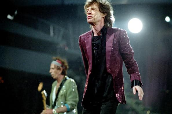 NETHERLANDS - JULY 31:  Photo of ROLLING STONES; Rolling Stones, Arena, Amsterdam, Nederland, 31 juli 2006, Pop, rock, rythm and blues, zanger Mick Jagger wandelt in, een lange paarse jas over het podium en kijkt over de camera heen, op de achtergrond speelt Keith op zijn gitaar  (Photo by Peter Pakvis/Redferns)