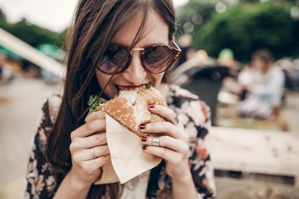 Junge Frau isst Burger
